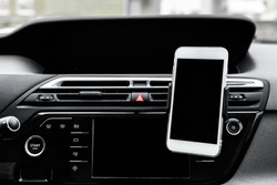 Modern smartphone device gadget mounted on phone holder at car dashboard.