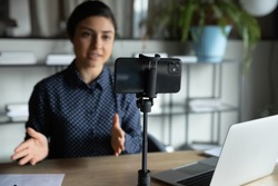 Modern smartphone gadget on tripod record young female speaker or coach making live broadcast on Internet, cellphone gadget shoot woman blogger or influencer talking for tutorial or webinar online