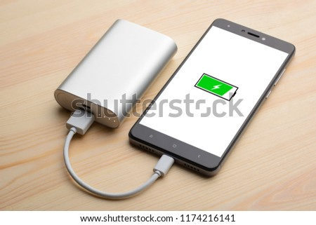 Modern smartphone lays on light wooden table while charging with power bank with quick charge. Illustration of green battery with lightning is on the mobile phone screen while charging #1174216141