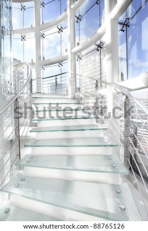 modern spiral glass stairs in a glass building