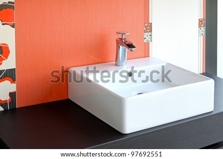 Modern square bathroom sink and red wall - stock photo