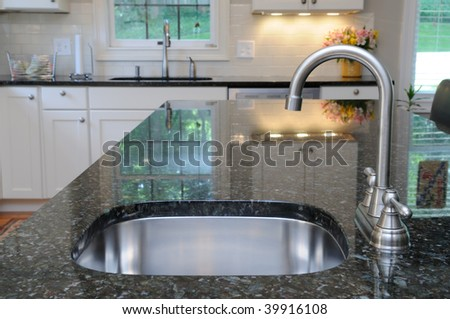 Modern stainless steel faucet and sink on kitchen island. Elegant granite counter.