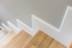 modern stair design with wooden tread and white riser, white skirting on wall, interior concept