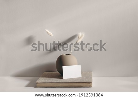 Modern stationery still life scene. Beige spheric vase with dry lagurus grass. Table background in sunlight. Blank business card mockups lean on old book. Champagne wall, long shadows.  Foto stock ©