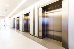 Modern steel elevator cabins in a business lobby or Hotel, Store, interior, office,perspective wide angle. Three elevators in hotel lobby.