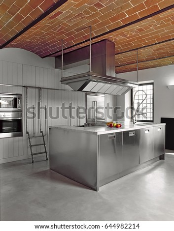 modern steel kitchen island with concrete floor and brick ceiling