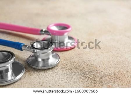 Modern stethoscopes on light background, closeup