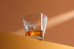 modern still life in warm colors. glass with whiskey with ice on the edge of the surface in the rays of light.