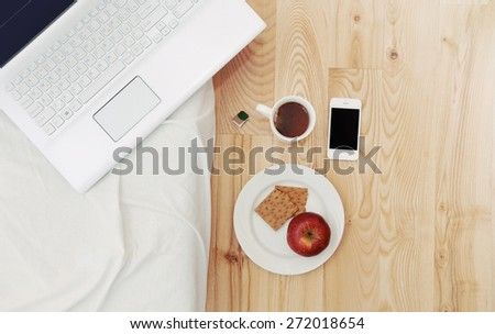modern still life of morning breakfast routine work place with computer device, stuff and some snack, lifestyle concept
