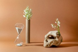 Modern still life with unusual natural stone, with bouquet of lilies of the valley and hourglass. Concept of anti-aging care products. Empty podium for cosmetics organic products and others.