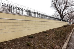 modern stone wall surrounding a protected area. brick new modern expensive street fence to the street. Wall fence sectional plastered with embossed road putty. Wall with barbed wire fencing