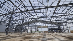 Modern storehouse construction site, structural steel structure of new commercial building against. Construction of modern factory or warehouse.