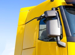 modern, streamlined truck cab with good aerodynamics with a rearview mirror. Yellow truck cab, background