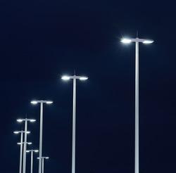 Modern street lights illuminated at night against a dark sky
