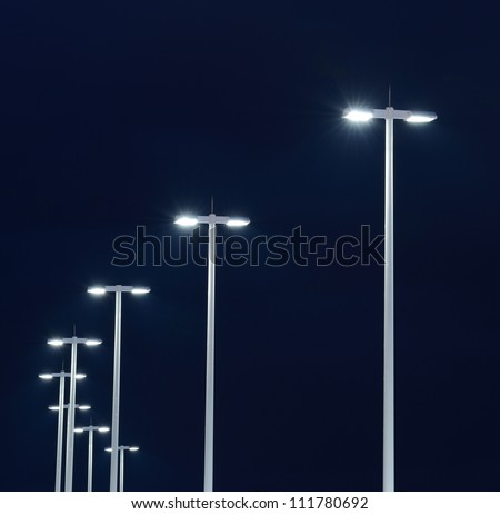 Modern street lights illuminated at night against a dark sky