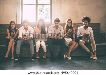 Modern students. Front view of young people using different gadgets while sitting close to each other in a row