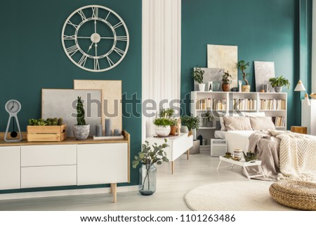 Modern studio apartment interior with cozy bedroom, white wooden furniture, designer decorations and plants #1101263486