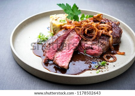 Modern style barbecue dry aged sliced roast beef with fried onion rings and mashed potatoes as closeup on a plate