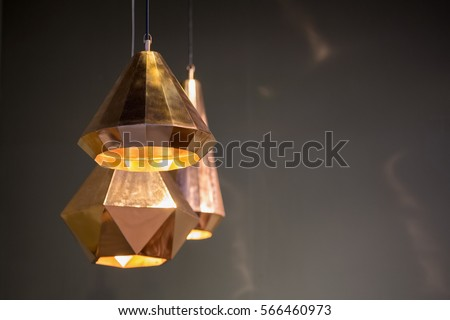 Modern style bronze decoration lamps and lampshades against dark  wall.