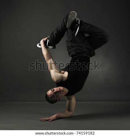 modern style dancer posing on grunge grey background - stock photo