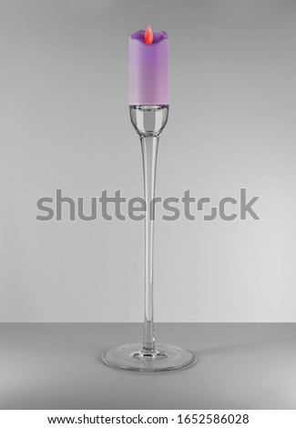 Modern style glass pastel purple coloured candlestick with candle and flame on the floor. Home decoration. Interior objects with clean grey background.