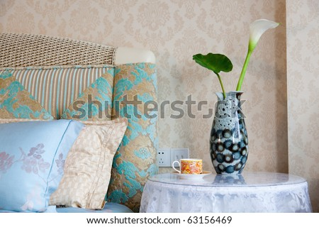 Modern style interior with with bed, pillows, bedside table,teacup and vase
