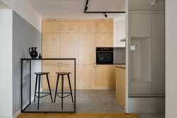 Modern style kitchen with birch plywood cupboards, black table with tall bar stools and concrete wall and ceiling