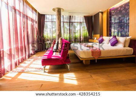 Modern style of living room with bed while sunlight pass through in morning in resort ,Thailand