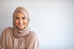 Modern, Stylish and Happy Muslim Woman Wearing a Headscarf. Arab saudi emirates woman covered with beige scarf.