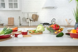 Modern stylish kitchen interior with vegetables and fruits on the table . Bright white kitchen with household items . The concept of a healthy lifestyle.