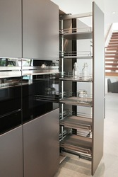 Modern stylish kitchen. Pull-out kitchen drawer in the kitchen for bottles. Black oven built in tall cabinet.