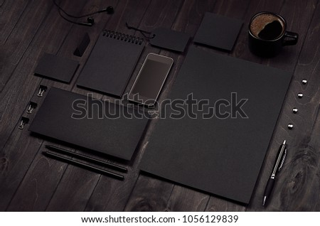 Modern stylish working place with blank black stationery, phone, cofee on dark wood board, inclined. #1056129839