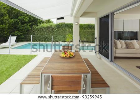 Modern suburban backyard and living room with table setting and swimming pool