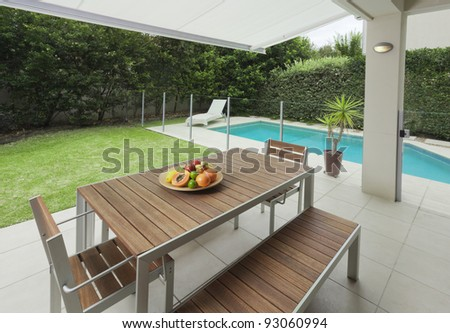 Modern suburban backyard with table setting and swimming pool
