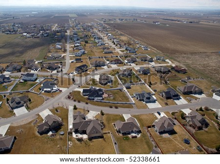 Modern suburban homes and farm fields in the midwestern United States.