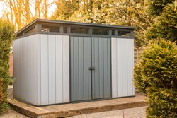 Modern summer house made of plastic. Gray garden shed for garden tools.gray garden shed made of plastic. Modern tool shed