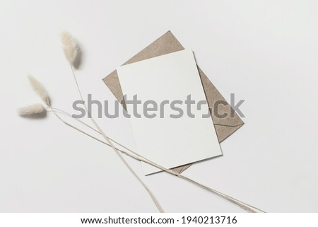 Modern summer stationery still life. Lagurus ovatus foliage and craft envelope. Blank greeting card mock up scene with bunny tail grass isolated on white table background. Flat lay, top view. Foto stock ©