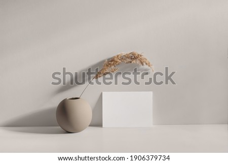 Modern summer stationery still life scene. Beige spheric vase with dry lagurus grass. Table background in sunlight. Blank paper card, invitation mockups lean on champagne wall, long shadows.  Foto stock ©