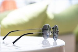 modern sunglasses rest on the coffee table at the beach