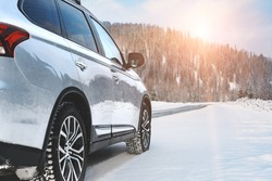 Modern Suv four wheel drive car stay on roadside of winter road. Family trip to ski resort concept. Winter or spring holidays adventure. car on winter snowy road in mountains in sunny day.