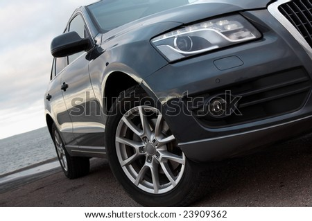 Modern SUV headlight and front wheel closeup
