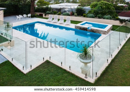 Modern swimming pool covered with glass panels beside a green lawn garden including trees and chairs