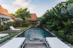 Modern swimming pool with comfortable rattan deckchairs and umbrellas standing on poolside near luxurious villa against green natural background with exotic foliage