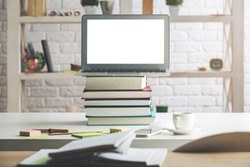 Modern table with empty white laptop screen, smartphone, supplies, book pile and other items. Close up. Creative designer office, education, occupation, freelance and lifestyle concept. Mock up