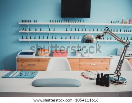 Modern table with nails color palette and lamp situating in salon. Interior concept #1054111616