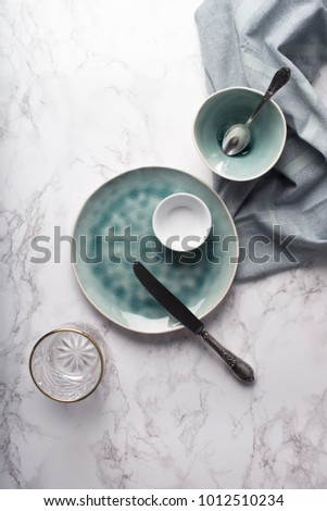 Modern tableware from above. Empty glass, plate and bowls with napkin on marble counter. Copy space. #1012510234
