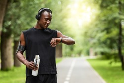 Modern technologies and active lifestyle. African sportsman working out with fitness bracelet, drinking water, blurred park background, copy space