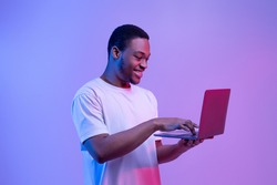 Modern Technologies. Happy Black Man Using Laptop Computer In Neon Light, Enjoying Online Communication, Gaming And Remote Job Offers, Excited Guy Standing Over Purple Studio Background, Copy Space