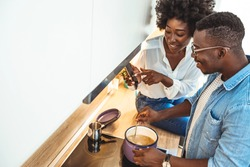 Modern technologies in everyday life. Black couple using smartphone and cooking dinner in kitchen together, copy space. Shot of a young couple preparing a meal together at home