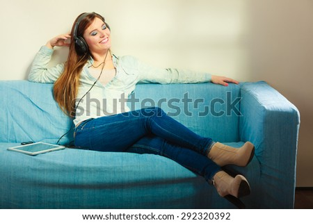 Modern technologies leisure and lifestyle concept. attractive woman student girl with headphones sitting on blue couch using tablet